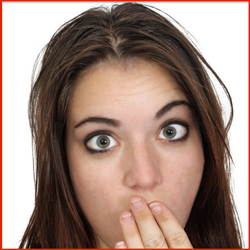 A close-up of an attractive brunette with bare shoulders and her hand over her mouth as if secretive or embarrassed.
