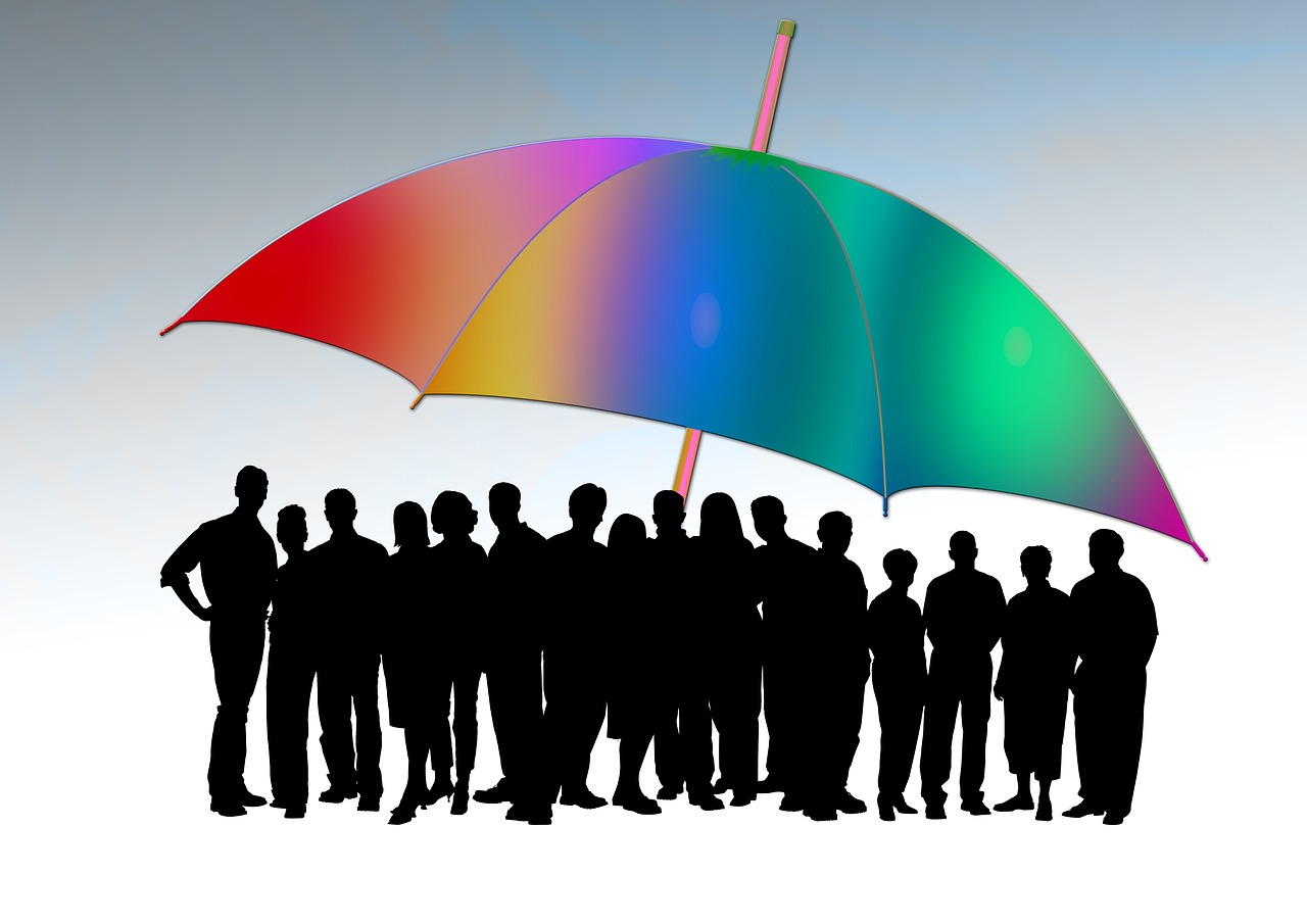 people silhouettes under colourful umbrella